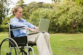 Young woman in the park using a laptop in her wheelchair