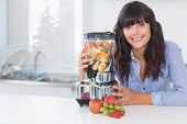 Happy brunette with juicer full of fruit at home in kitchen