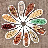 Nut selection in white porcelain dishes over hessian background.