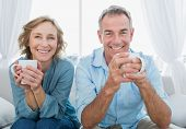Smiling middle aged couple sitting on the couch having coffee looking at camera at home in the livin