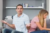 Couple sitting back to back after a fight on the couch with man gesturing at camera in sitting room at home