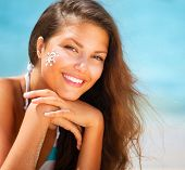 Suntan Lotion Woman Applying Sunscreen Solar Cream. Beautiful happy cute Girl applying Sun Tan Cream