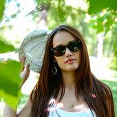 fashion girl outdoor portrait, young woman walking in summer park  in sunglasses and fedora with lon