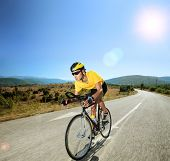 Male cyclist riding a bike on an open road on a sunny day, shot with a tilt and shift lens