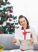 Happy Young Woman Reading Christmas Postcard Near Christmas Tree