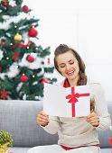 Happy Young Woman Reading Christmas Postcard Near Christmas Tree