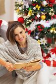 Happy Young Woman Reading Book Near Christmas Tree