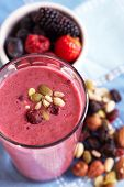 stock photo of dry fruit  - Two glasses of berries smoothies topped with dried fruits and nuts - JPG