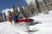 stock photo of friendship day  - Couple driving snowmobile on snow covered track - JPG