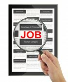 Searching for a job with a magnifying glass in a digital tablet