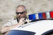 stock photo of illegal  - Closeup of a police officer using two way radio by police car - JPG