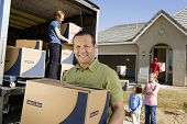Portrait of a smiling man with box while family unloading delivery van in the background by new hous
