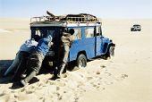 Men pushing jeep in desert