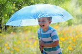 Rain and sunshine with a smiling boy holding an umbrella and running through a meadow of wildflowers