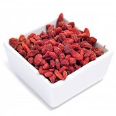 a bowl with dried goji berries on a white background