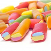 closeup of a pile of liquorice candies of different colors on a white background