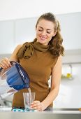 stock photo of pitcher  - Happy young housewife pouring water into glass from water filter pitcher - JPG