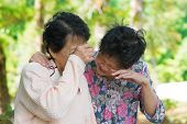 stock photo of condolence  - Sad senior Asian women  in grieving the loss of a loved one - JPG