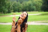 Young happy woman walking in the rain