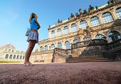 Young lady tourist standing in front of old building (Zwinger) in Dresden