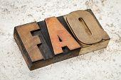 frequently asked questions - FAQ acronym - text in vintage letterpress wood type on a ceramic tile b