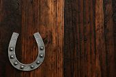 Small decorative horseshoe on rustic wood background with copy space.  Low key macro with directional, natural lighting for effect.