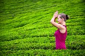 image of surya  - Praying woman with hands in namaste in red cloth on tea plantations in Munnar hills Kerala India - JPG