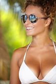 Bikini girl wearing sunglasses on palm tree beach. Beautiful young asian woman enjoying summer sun on tropical beach