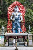 FUKUOKA, JAPAN - FEBRUARY 9, 2013: A worshiper under the large Cetaka, a god devoted to the protecti
