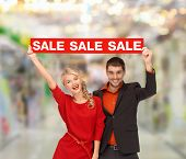 shopping, sale, christmas, couple and mall concept - smiling woman and man with red sale sign at shopping mall