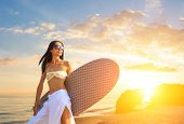 Asian woman with surfboard on the beach at sunset