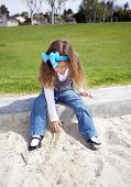 Young beautiful 3 years old girl playing in the sandbox in the park