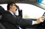 stock photo of yawning  - Asian Exhausted driver yawning and driving  car - JPG