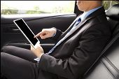 Businessman Working In Back Of Car And Using A Tablet