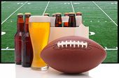 Six pack of beer and frothy glass with an American Football in front of a big screen television. Gre