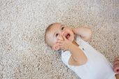 stock photo of cute innocent  - High angle view of a happy cute baby lying on carpet at home - JPG