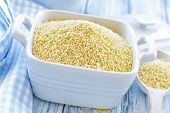 stock photo of millet  - Raw millet in a bowl on a wooden table - JPG