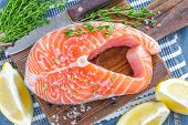 pic of redfish  - Raw salmon on a chopping board with fresh lemon - JPG
