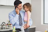 stock photo of half-dressed  - Well dressed father carrying daughter while on call in the kitchen at home - JPG
