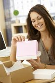 Happy young woman opening parcel, looking at gift box, smiling happy.