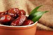 Dried dates in bowl on table on sackcloth background