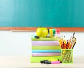 School supplies on table on blackboard background