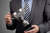 Businessman celebrating with trophy award for success in business or first place sporting championsh
