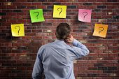 Choice and decisions: businessman thinking with question marks written on adhesive notes stuck to a