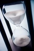 stock photo of pass-time  - High angle close up view of sand running through an hour glass or egg timer measuring the passing time and counting down to a deadline - JPG