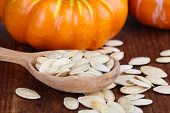 Pumpkin seeds in spoon with pumpkins on wooden background