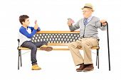 Grandfather playing cards with his nephew seated on bench isolated on white background