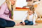 Girl sitting with mother on floor playing with wooden toy spinner