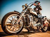 MOSCOW, RUSSIA-JULY 7, 2013: Biker girl on legendary bike Harley Sportster (focus on the wheel).Harl