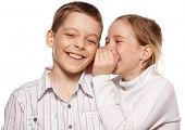 Girl whispers boy in the ear secret. Children gossip